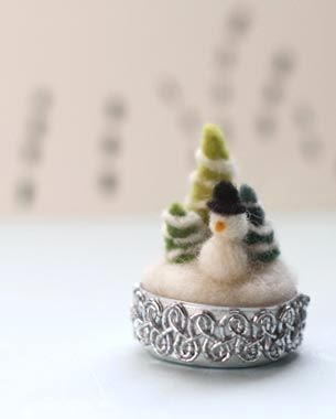 tiny needle-felted snowman and trees, sitting in a tea light tin.