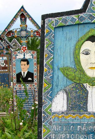 Colourful Cemetery — Sapanta, Romania. Each grave site is marked with a brightly coloured tombstone that depicts either the person buried or a memorable scene from their life. Many tombstones include a funny epitaph or poem.
