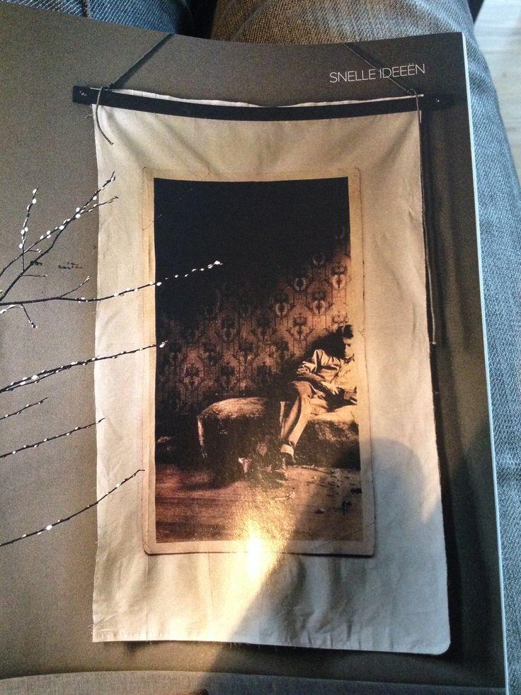 Een foto krijgt een nieuw leven door het beeld uit te laten vergroten en het op doek te laten printen. De stof zit tussen 2houten latten geklemd, die met een touw aan de muur hangen.