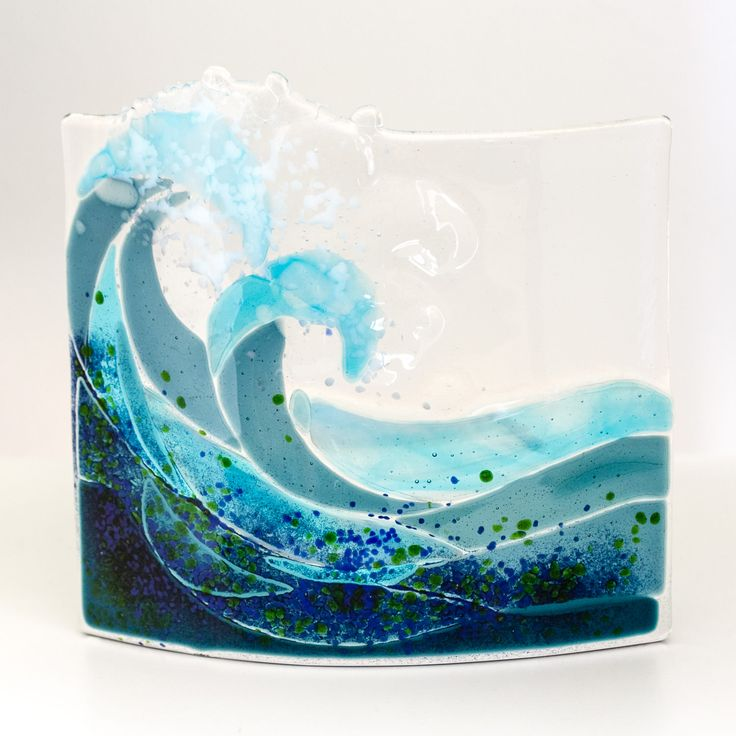 A curved piece of fused glass the depicts two waves crashing, something that is often seen along the ...