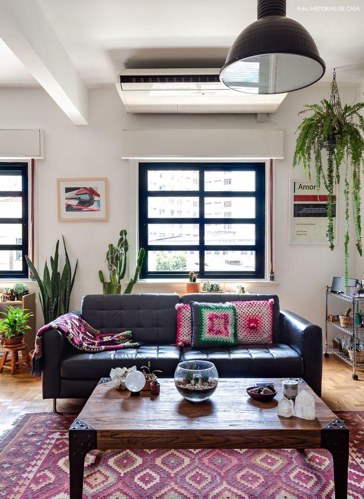 Sala de estar com muitas plantas, clima industrial e acessórios étnicos.