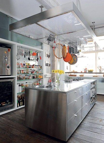 """Idealizada pela moradora Beia de Carvalho e seu filho, a cozinha é como um laboratório no qual eles preparam suas receitas. Moderna e organizada, tem ilha de aço e armários fechados por vidro. """"Quisemos tudo à mostra e à mão"""", diz"""