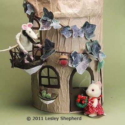 Miniature mouse and Calico Critter outside a simple house made from recycled materials.