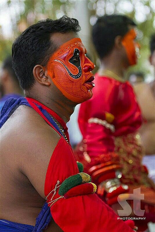Painting The Face of a Theyyam Performer. Theyyam also known as Kaliyattam, it is a ritual dance popular in north Kerala or the erstwhile Kolathunadu
