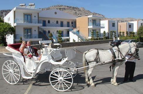 Bride and her father arriving by horse and carriage at Lindia Thalassa Pefkos for wedding at the Veranda. Image by Avalon photography Rhodes