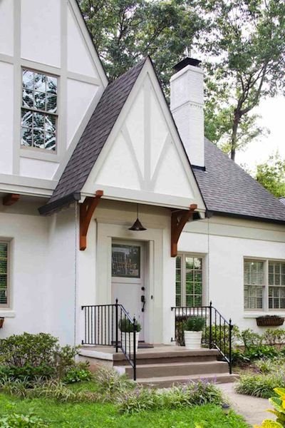 Tudor style home remodel with wood brackets, rain chain and muted exterior trim details.