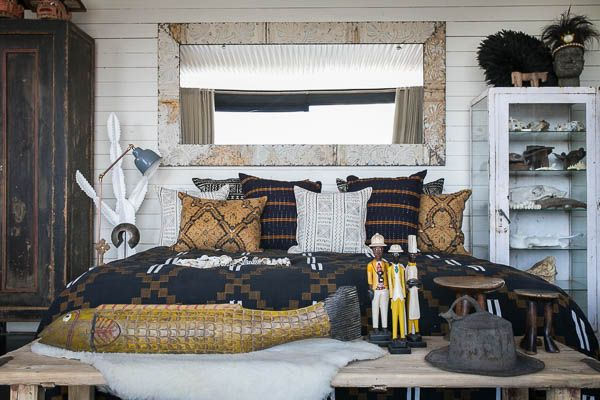 The bed is covered with a hand-stitched Kente cloth from the Ivory Coast, mud cloth, antique Batik and ash-oke scatter cushions and strings of shell necklaces from Papua New Guinea. Above the bed the Hunter-Gatherer has hung a mirror made from repossessed tin ceiling tiles.