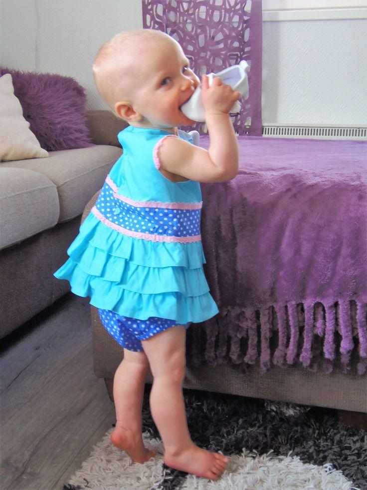 Miranda textilesin turkoosi röyhelömekko ja pilkulliset alushousut. Mekossa vaaleanpunaisia somisteita sekä vyötäröllä pilkullinen kaistale.