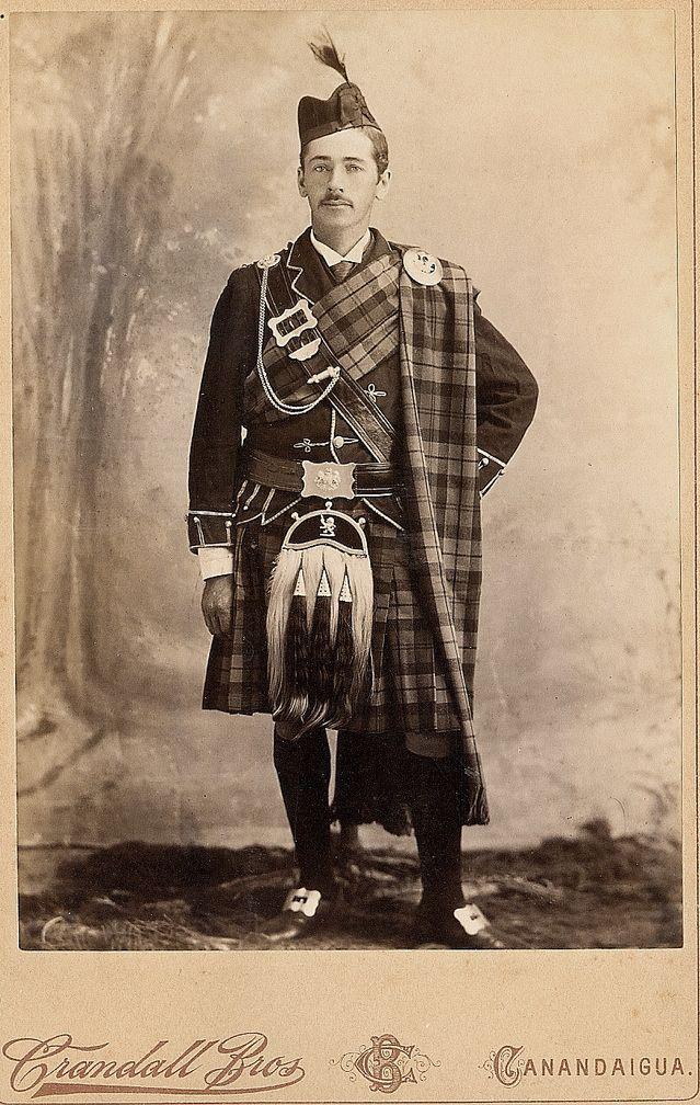 Man dressed in full highlander tartan.