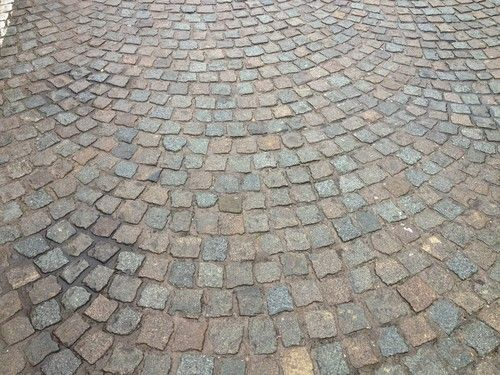 Reclaimed cobblestones in fan shaped pattern. I love the old stones. See more on this site.