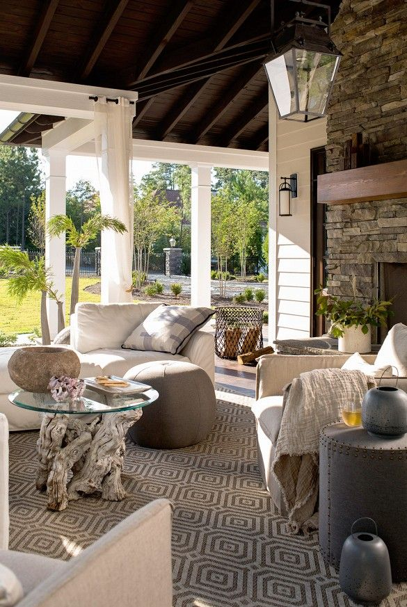 An exterior fireplace and neutral furniture set up on the front porch
