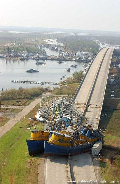 Hurricane Katrina aftermath. Many area boats are damaged or destroyed, in the background boats that were sunk by the storm remain in the waterway   Southern Louisiana, September 12, 2005 -fema/illinoisphoto.com- Large boats remain on this road, closing it to traffic.