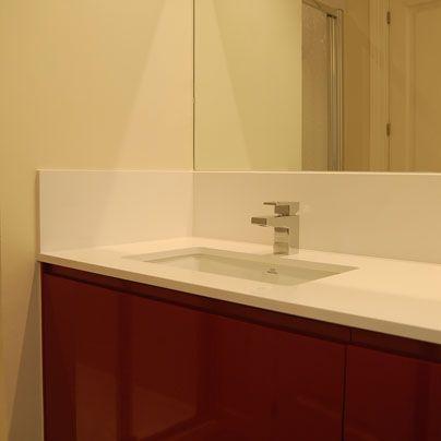 Ba o con mueble granate y encimera blanca de silestone for Encimera bano silestone