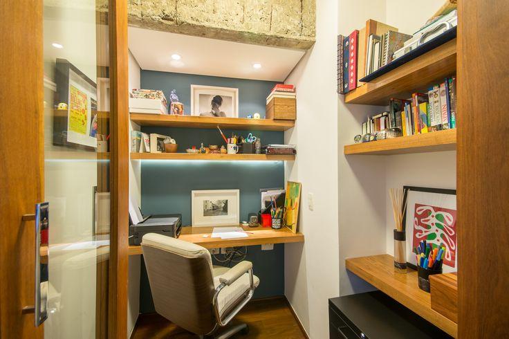 Home Office em apartamento. Bancada e prateleiras com acabamento em freijó e fitas de LED, parede azul de fundo, piso de madeira, forro de gesso com spots e viga em concreto aparente