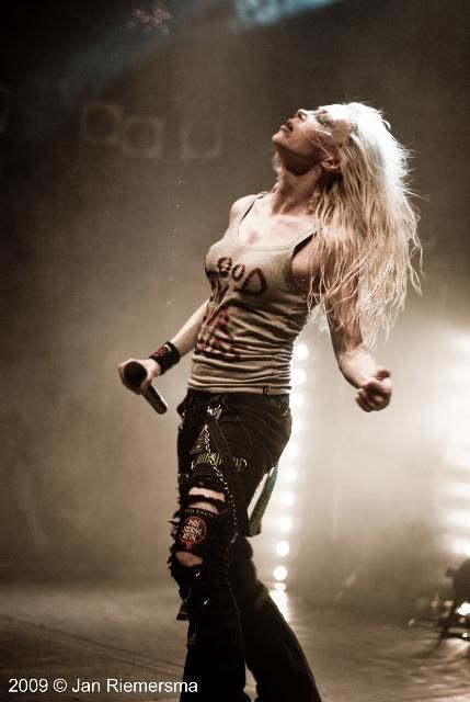 Angela Gossow (Arch Enemy) Live in Rijssen, NL 2009. The fog and the lighting in this are nice, although I'm thinking some sort of filter may have been used, I dunno. It's a great shot, she has her arms open and her eyes closed, like she's just soaking up the music and the crowd. She's sinewy and pretty, too. This woman has a voice that would peel paint right off your walls.