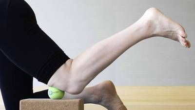This exercise with a therapy ball (or a tennis ball) can help ease knee pain and stiffness by digging into the suprapatellar pouch, massaging the area where the quadriceps muscles converge, loosening tightness and allowing the knee to track more smoothly.