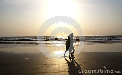 Two friends silhouetted in Arambol Beach, North Goa, with Sun setting at the backdrop.