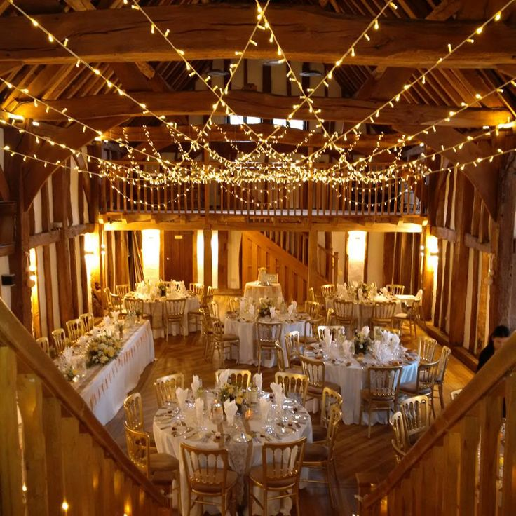 A beautiful cross over canopy in true warm white with draped lights over the bannisters #barnwedding #weddinglighting #fairylights #buckinghamshire.