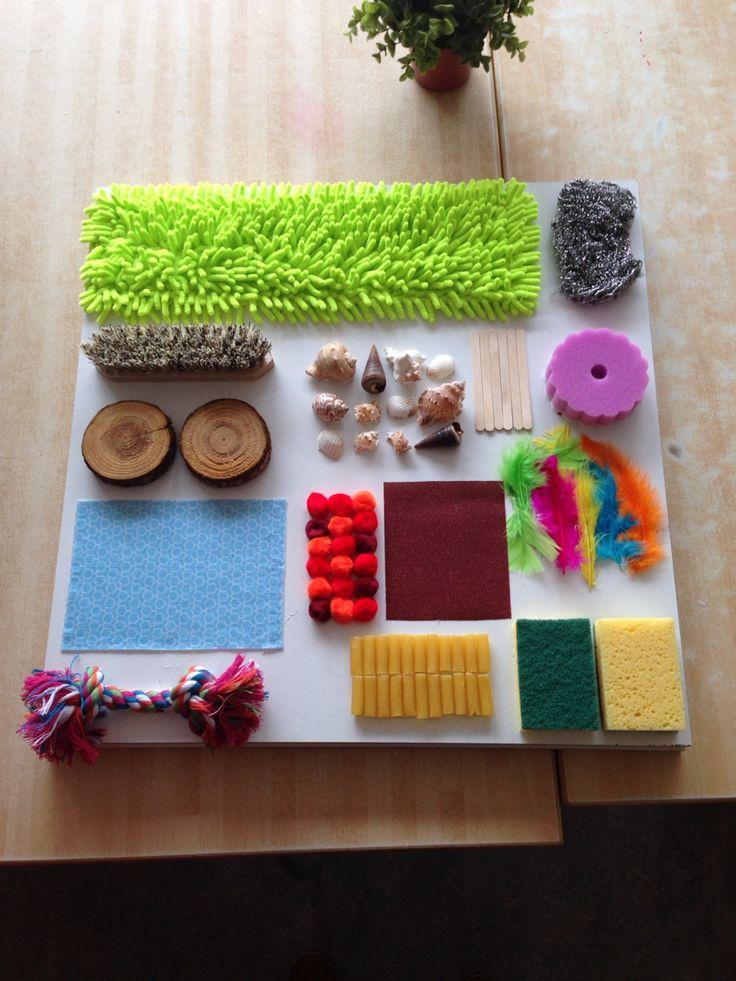 GERECYCLEERD/ZELFGEMAAKT MATERIAAL : Kleef verschillende materialen op een houten paneel. Het kind kan rond/ over het paneel kruipen en met de handjes aan de verschillende dingen voelen.