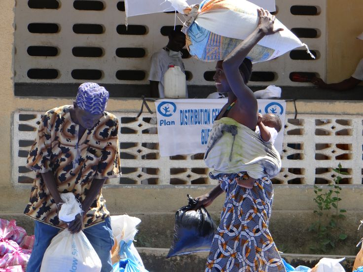 Una mujer carga con su ración de comida en Guinea Conakry.