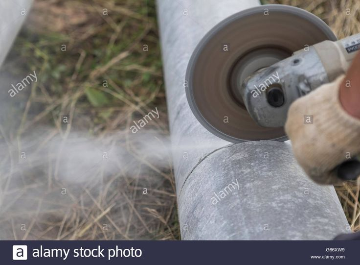 Download this stock image: Work sawing asbestos pipe for foundation electric tool - G66XW9 from Alamy's library of millions of high resolution stock photos, illustrations and vectors.