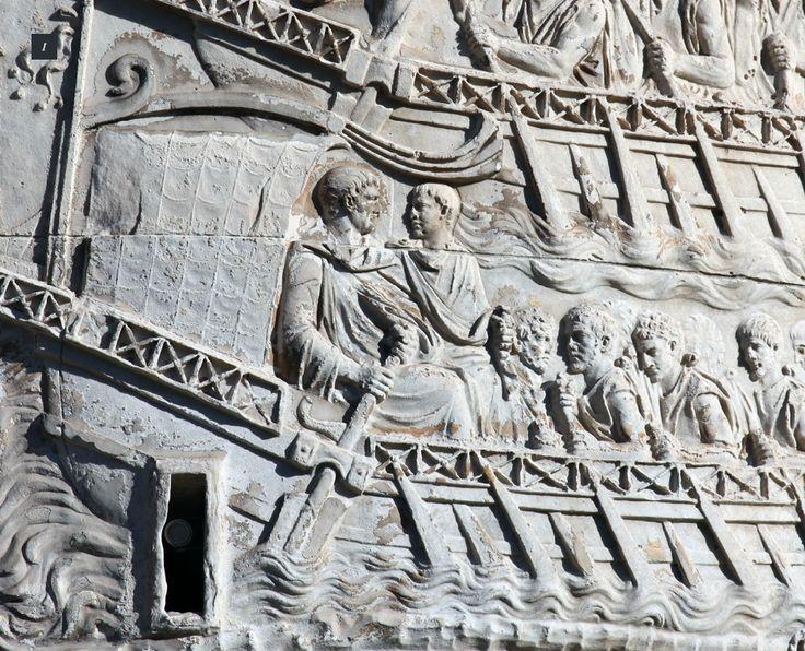 Un pinten stâncos separă apa curgătoare în două ramuri. Pe ramura de jos este reprezentat Traian în ipostaza de conducător al flotei principale, care parcurge această porţiune ce are ca punct final poarta de apus a cetăţii Tropaeum Traiani. Putem deduce faptul că această ramură este chiar râul pe malul căruia a fost ridicată cetatea Tropaeum Traiani.