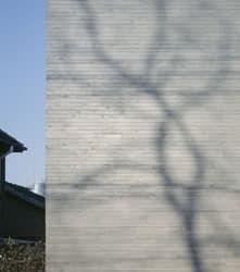 Casa del arquitecto chino Zhang Lei, de expresión minimalista, con acabado en hormigón de textura de ladrillo. Hendiduras en fachada para iluminar escalera y huecos.