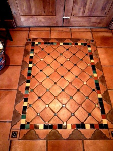 Saltillo tile rug in lay.  Border is cut pieces of terracotta and manganese Saltillo Fleur de Lis shapes mixed with solid color glazed hand painted tiles.