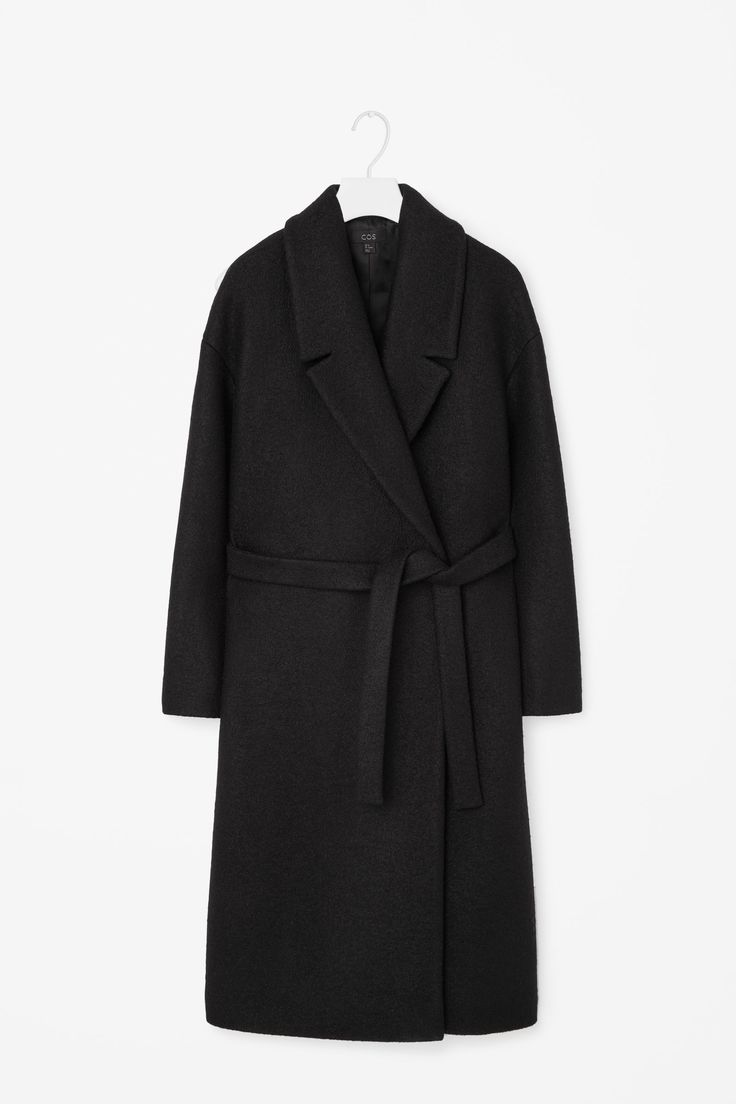 This coat is made from extra-soft wool with a matching fabric tie fastening around the waist. Slightly oversized, it has a crossover front, wide notched lapels and subtle in-seam pockets. It is secured with hidden front buttons.