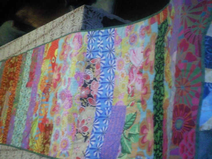 bed runner made with kaffe fasset fabrics done in the jelly roll quilt race but with 4 inch strips for cousin colleen's 60th.