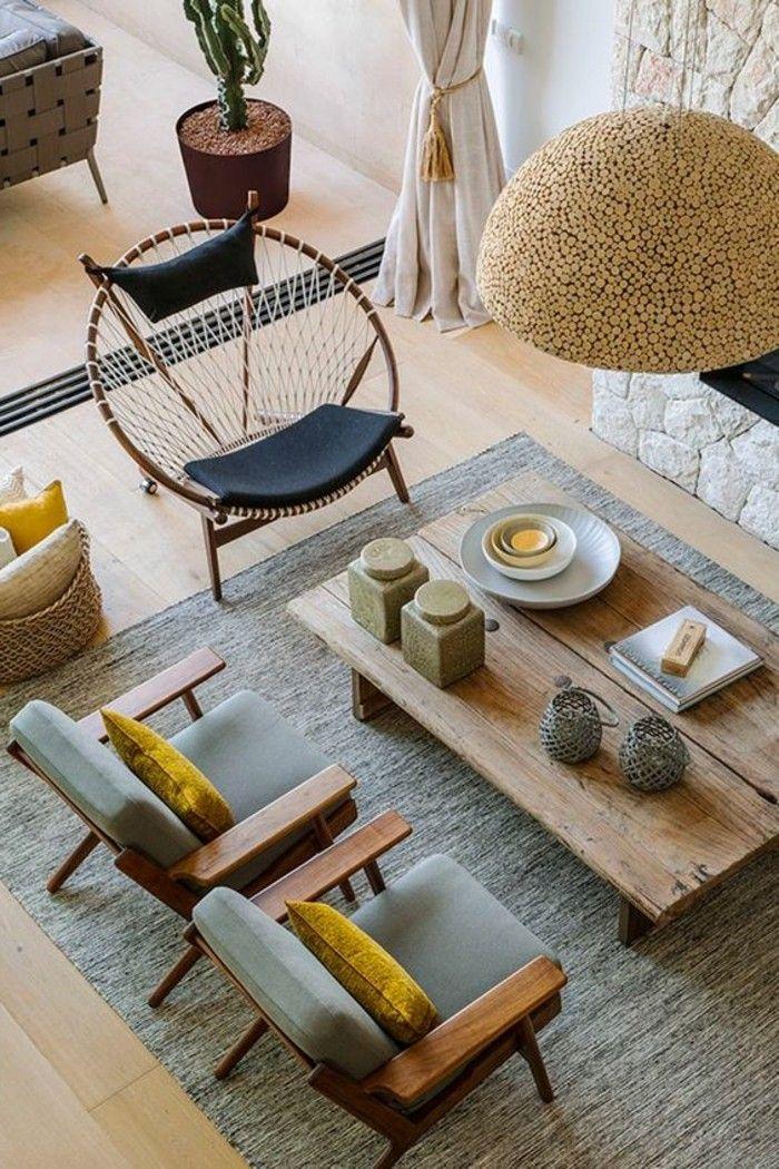 couleur jaune moutarde, deux chaises grises, grande table en bois et plafonnier exotique