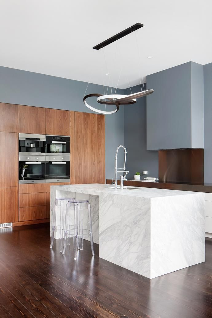 No overhead cupboards. The island is Calacatta marble, mitred and book-matched so it appears as a monumental block. The joinery is American walnut veneer and the benchtop and splashback are matt stainless steel.