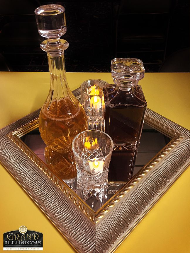 Liquor decanters on a mirror with tea lights in the glasses as a table centerpiece