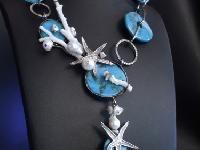 Collana in argento 925 lavorata a mano , composta da anelli martellati e stelle marine in argento, con turchesi, perle di acqua dolce e rami di…