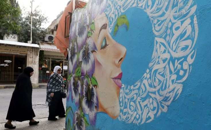 Women walk past a graffiti mural in the Jordanian capital Amman, where street artists are increasingly looking to brighten up the drab streets (AFP Photo/Khalil MAZRAAWI)