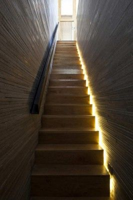 Straight staircase with side lit void and unusual folded steel handrail. By:Freshome