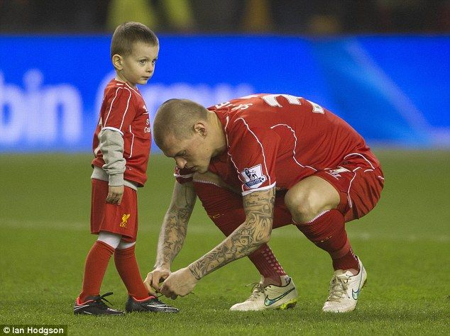 Skrtel senior bends down to tie his son's shoelaces ahead of the victory against Tottenham...