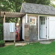 The oversize door and a birdhouse tucked in the gable reinforce the garden shed's dollhouse proportions, echoed in a second shed added nearby, complete with a bath. The space also served the outdoor dining area: With plates, forks, and salt and pepper close at hand, there are fewer trips back and forth to the kitchen.
