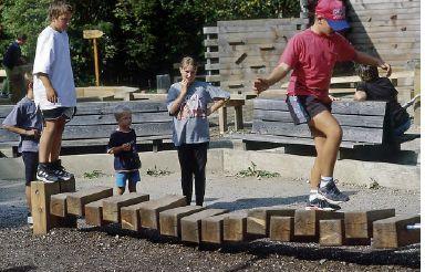 En balansutmaning bestående av ett antal träkubb som är trädda på två stålvajrar. Placeringen av borrhålen varierar från kubb till kubb vilket resulterar i att de olika kubbarna ger skiftande respons vid belastning.  6.51700 - Balance blocks 6.51701 - Balance blocks, med ändstativ i varmförzinkat stål