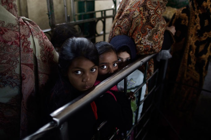 Pakistani girls line up to receive a ration of rice during food distribution at the shrine of the Sufi saint Beri Imam.