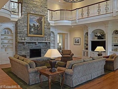 Two story great room with floor to ceiling stone fireplace for Great room flooring ideas