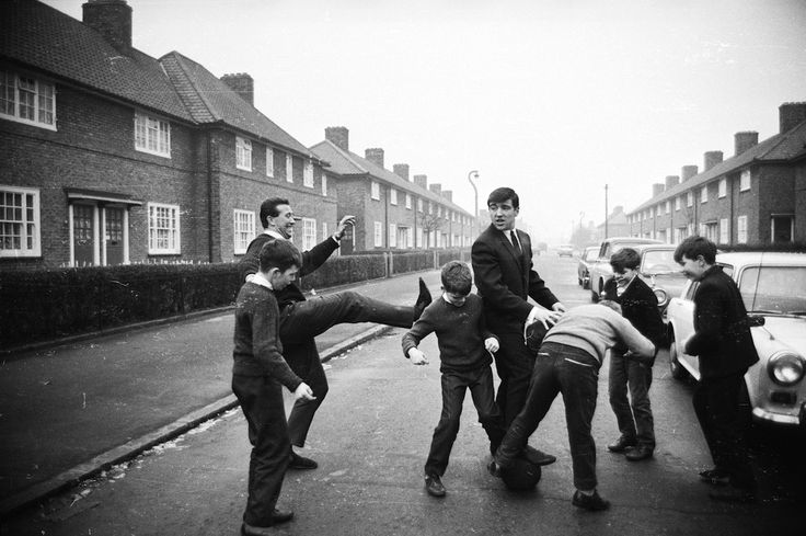 JANUARY 1965: ENGLISH FOOTBALLERS KEN BROWN (LEFT) AND TERRY VENABLES PLAY FOOTBALL WITH A GROUP OF CHILDREN IN BONHAM ROAD, DAGENHAM – THE STREET WHERE THEY WERE BORN.