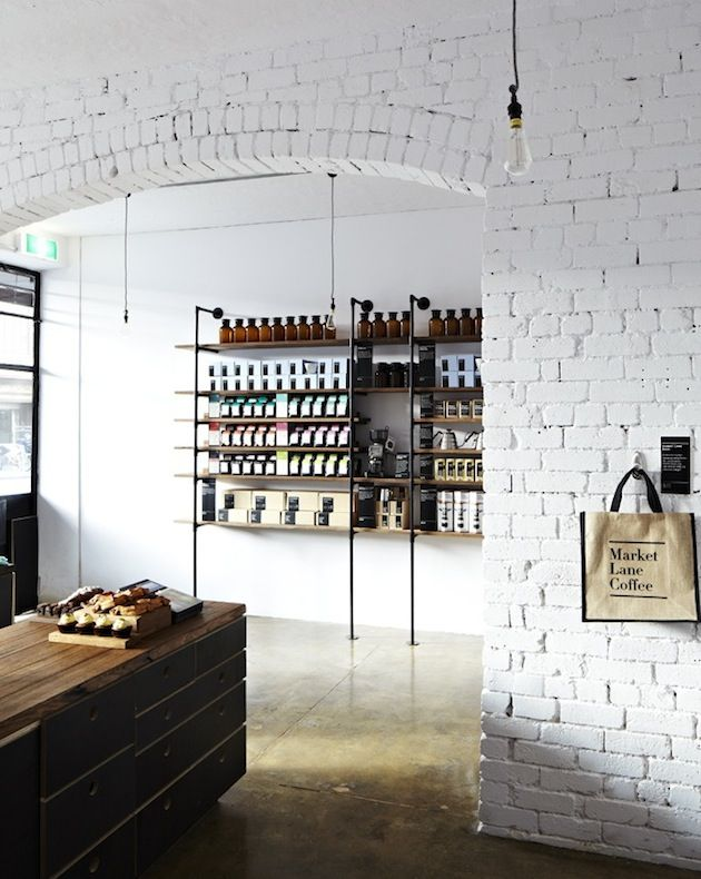 market lane coffee exposed brick wall painted white concrete floor aged wood and industrial minimal shelves and table - Painted Wood Cafe Decoration
