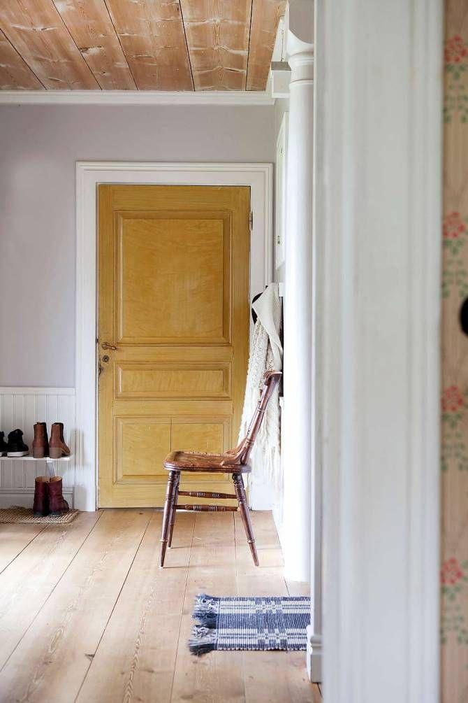 JORDNÄRA färger och avskavda material samsas fint i den rymliga hallen. Det breda brädgolvet, innertaket och badrumsdörren i ockragult har bevarats.