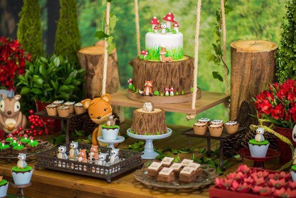 A festa de primeiro aniversário do pequeno contou com uma pegada rústica de floresta repleta de bichinhos fofos e uma identidade visual e layout com as cores vermelha escura, tons terrosos e azul-c…