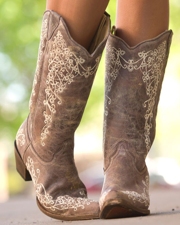 Dark brown distressed leather cowboy boots decorated with whimsical floral embroidery etched in cream-colored thread. These vintage boots are so soft, making them a comfortable fit for all-day wear. You will love the simple details and versatile colors of these boots, as they will pair easily with any outfit in your stylish wardrobe. Grab your favorite pair of blue jeans or summer sundress and hit the town in these precious Corral boots.