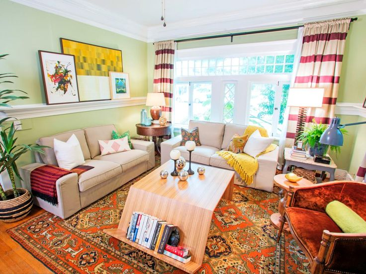 HGTV's Design on a Dime transformed this craftsman living room with an eclectic makeover. A bold area rug and striped curtains pair with neutral love seats to define the seating area. Decorative molding doubles as a ledge for collected artwork, while the sculptural coffee table keeps a low profile with a shelf for books.