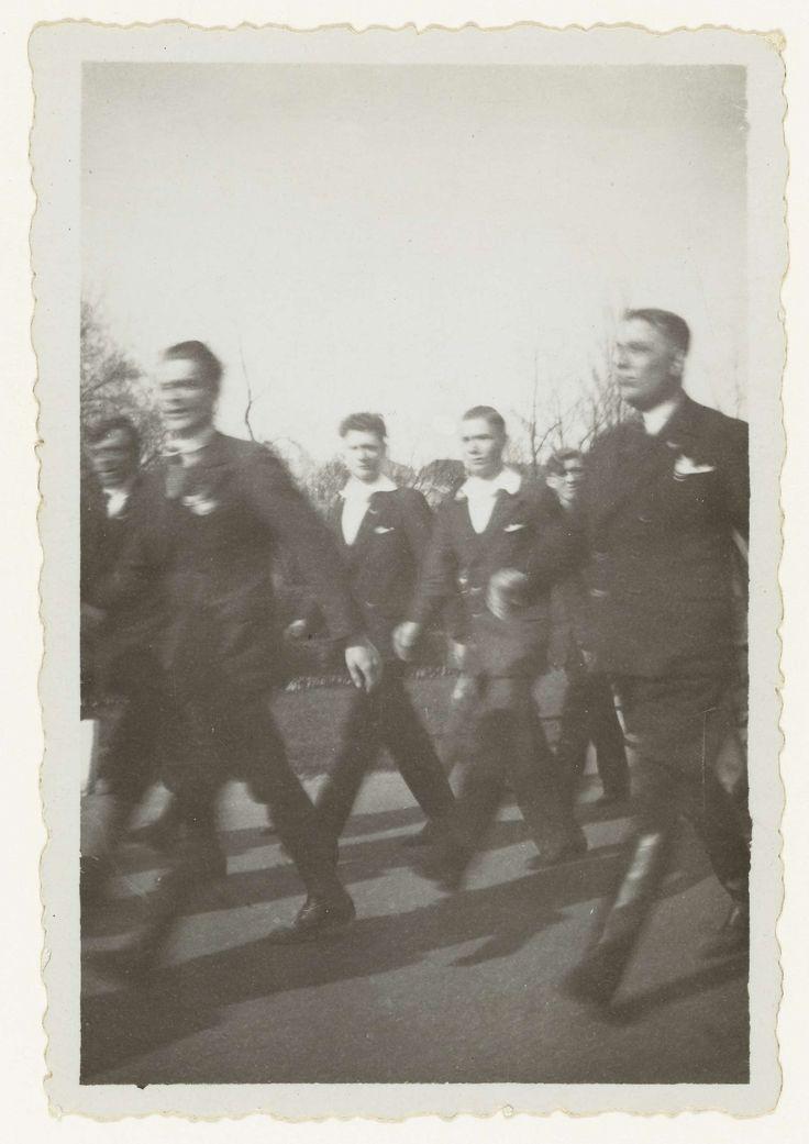 Anonymous | Optocht NSB, Anonymous, 1936 - 1937 | Optocht van de NSB. Voorop twee mannen in hoge zwarte laarzen. Niemand is in uniform. Vanaf 1936 gold voor de NSB en aan hen verwante organisaties een verbod om in uniform op straat te verschijnen.