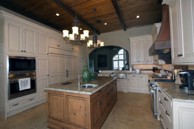 This traditional kitchen features a slide out spice rack and a wine cooler built into the island.