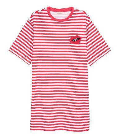 Röd/Vitrandig. En t-shirtklänning i bomullstrikå med ränder. Klänningen har en applikation upptill och kort, vid ärm. Ofodrad.